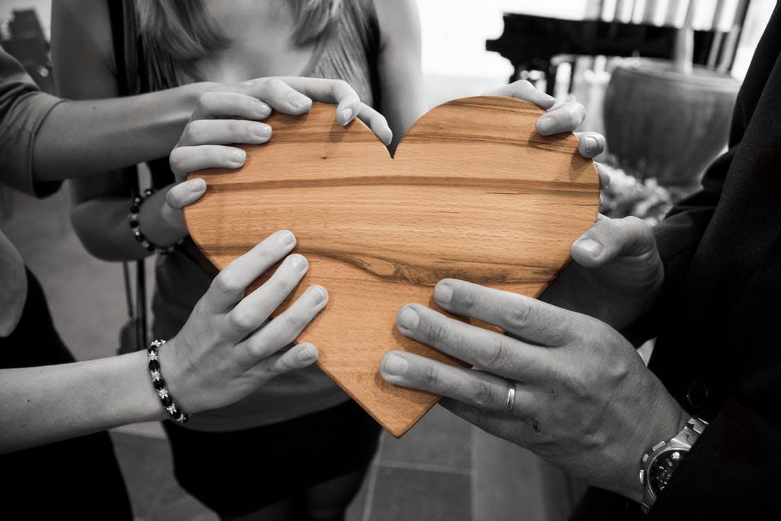 HEEL communicatietrainingen hart van hout vastgehouden door 6 handen