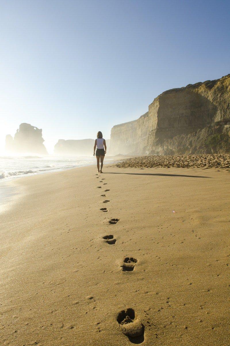 assertiever worden wandelaar op strand voetstappen