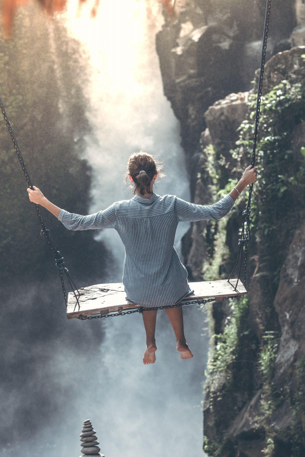 comfortzone vrouw op een hoge schommel boven diepte