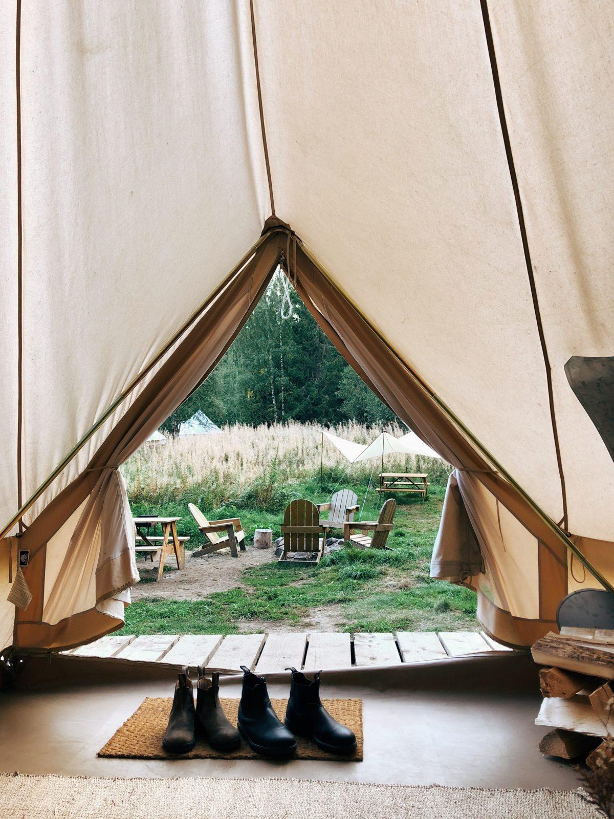 comfortzone tent voorkant open uitzicht over gras waar stoelen staan. Twee paar schoenen staan op een matje in de tent.