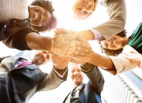 communiceren vanuit verbinding team staat in een kring met handen op elkaar