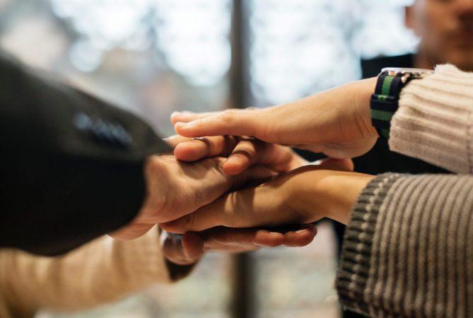 Uitgestoken handen van teamleden op elkaar