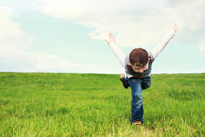 Persoonlijke ontwikkeling. Voorovergebogen klein jongetje in een groot groen veld op een been met uitgestrekte handen