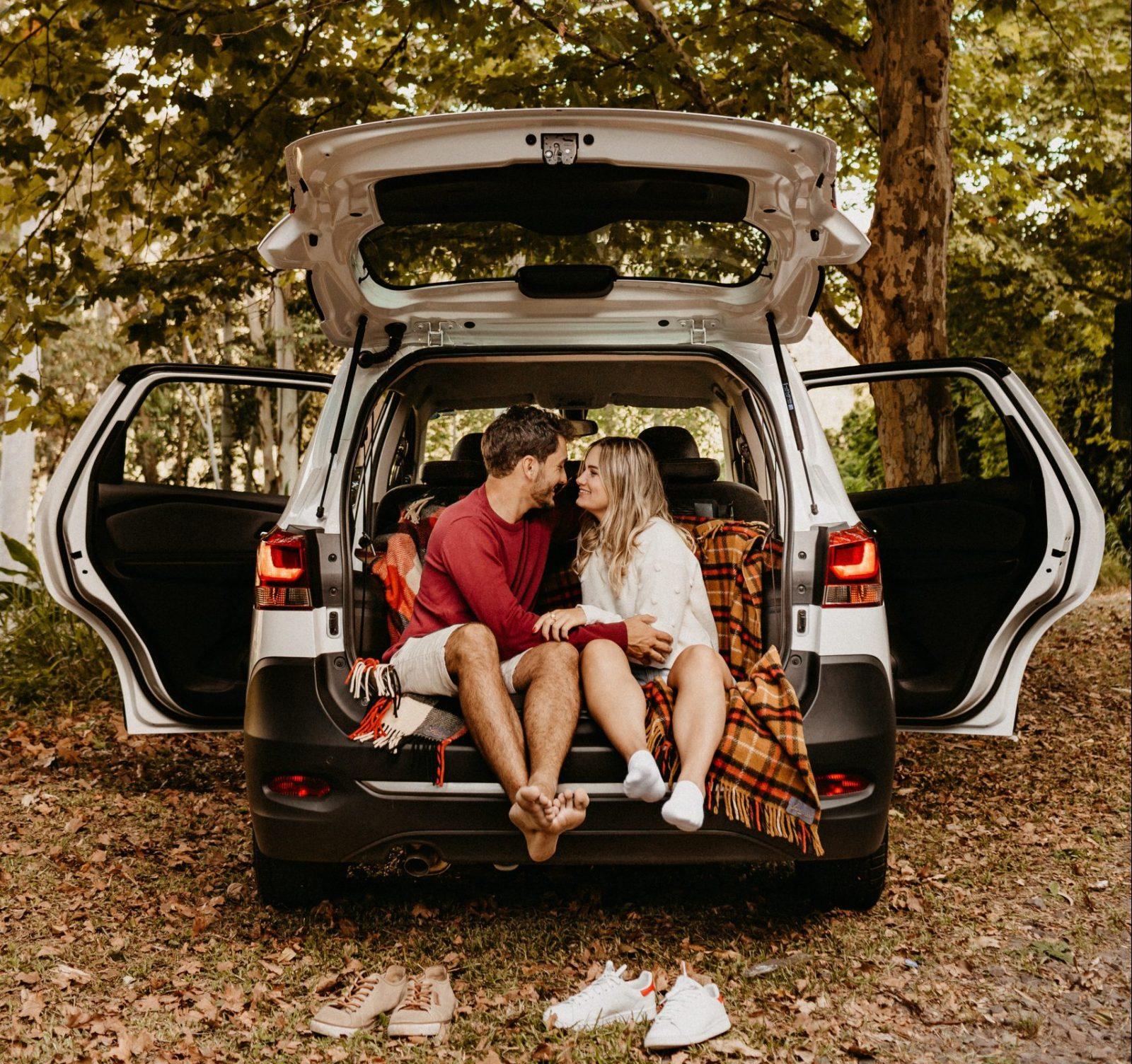 geluk verliefd jong stel in kofferbak auto