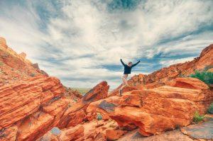 keuzes maken vrouw op een lopend over een rots met handen omhoog
