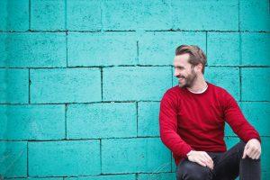 Zelfvertrouwen, lachende blij kijkende man met rode trui voor een blauwe muur