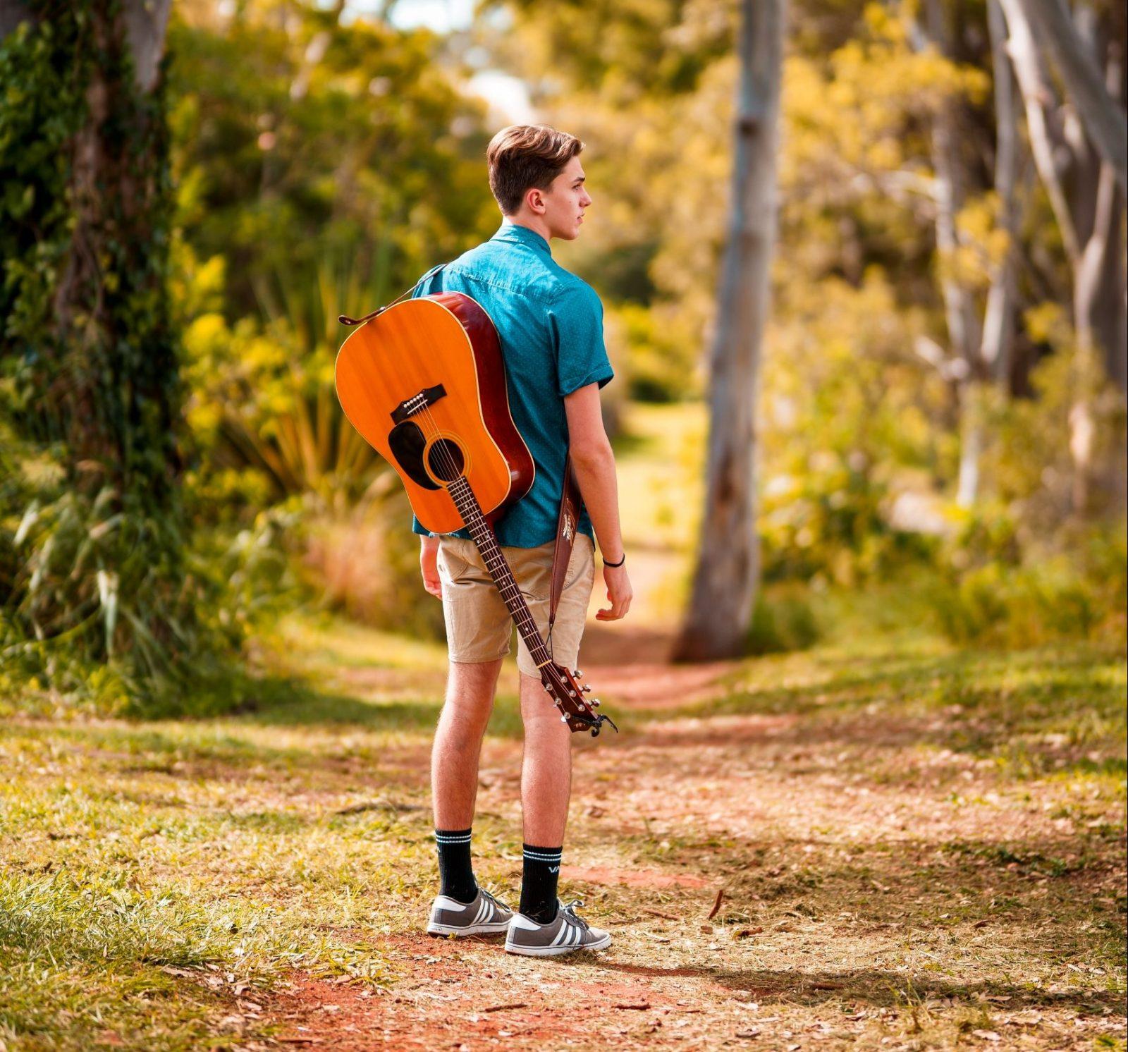 opkomen-voor-jezelf-jongen-gitaar-bos