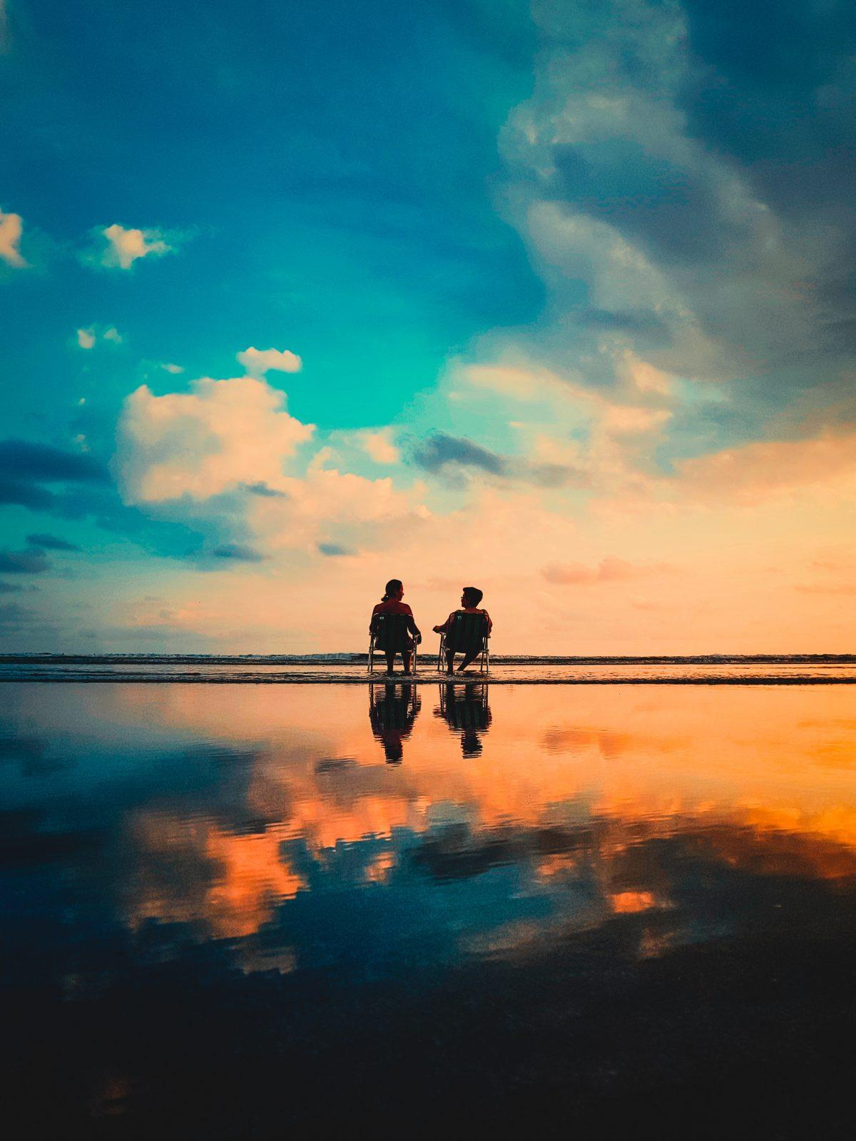 persoonlijk leiderschap man en vrouw zittend op een strandstoel in zee bij zonsondergang