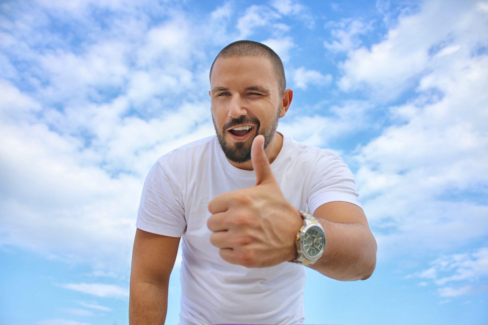 persoonlijke effectiviteit man geeft een knipoog en houd zijn duim omhoog