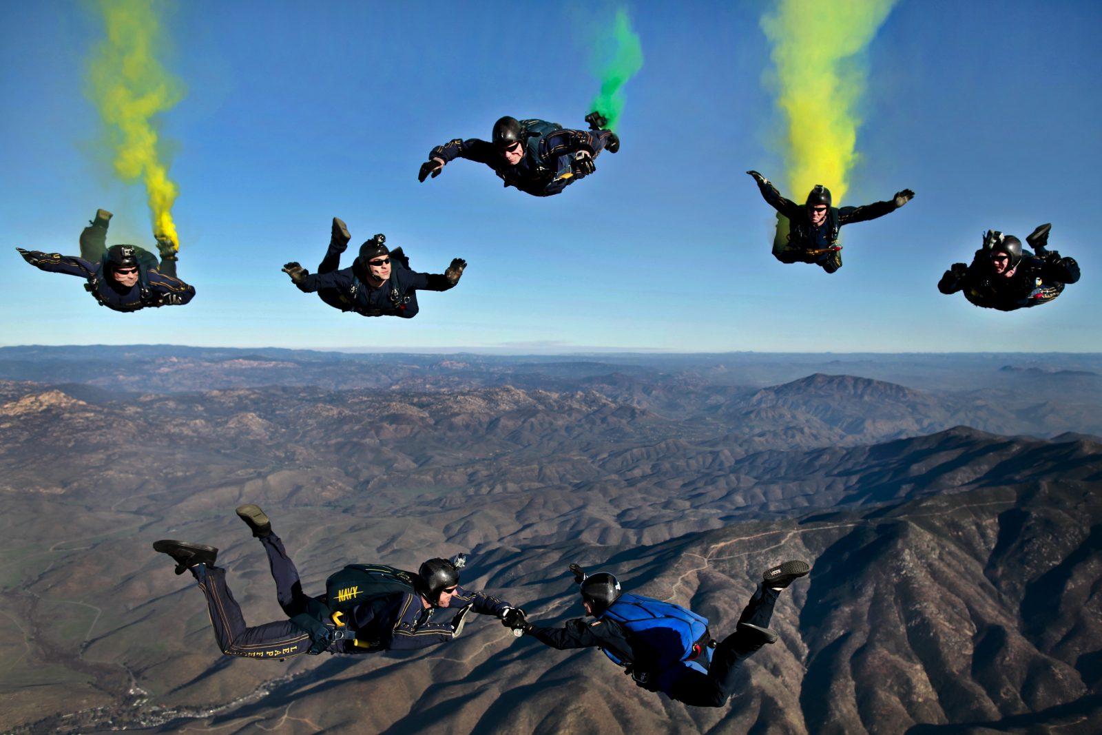 teamontwikkeling 7 parachutisten werken samen in de lucht om een eenheid te vormen