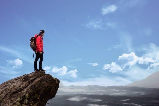 training persoonlijk leiderschap man op een rots kijkend naar de blauwe lucht